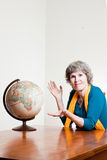 Where to go traveling. Mature woman trying to decide where to go in her retirement Exploration of earth and retirement theme Stock Images