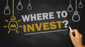 Where to invest. On blackboard background royalty free stock photography