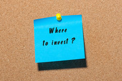 Where to invest hand writing qestion on blue sticker pinned at notice board Royalty Free Stock Photos