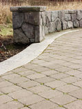 Where Walls Start. Endcap piece to the start of a beautiful stone mason wall which extends along the paved walkway Royalty Free Stock Photography