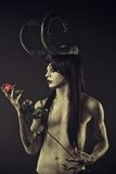 Where wild roses grow. Horned devil with red roses over black background Stock Photo