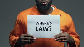 Wheres law question on cardboard in hands of Afro-American prisoner, disorder. Stock footage stock video