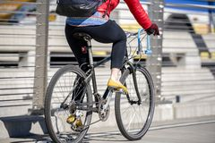Woman in leggings and jacket rides bike preferring healthy lifestyle stock images