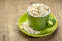 Whey protein powder in a coffee cup. Against textured bark paper stock photos