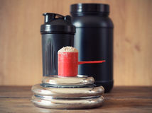 Whey protein. Powder in scoop with  plastic shaker on wooden background Royalty Free Stock Images