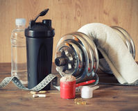 Whey protein. Powder in scoop with  plastic shaker on wooden background Stock Image
