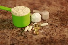 Whey protein powder in scoop with vitamins and on granite background. Selective focus,. Whey protein powder in scoop with vitamins. athletes require multiple Stock Images