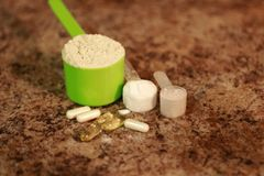 Whey protein powder in scoop with vitamins and on granite background. Selective focus,. Whey protein powder in scoop with vitamins. athletes require multiple Royalty Free Stock Photo