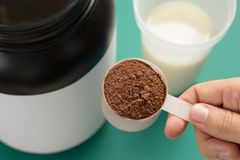 Whey Protein. Shaker with milk. Perspective, holding measuring scoop full of chocolate flavour powder on green background. Whey protein food supplement for stock photography