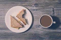 快餐休息放松使快餐吃破烂物不健康的营养概念变冷 在工作 与面包屑的被咬住的乳酪三明治在whi 库存图片