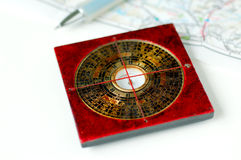 Which direction. Close up of asian compass and map Stock Images