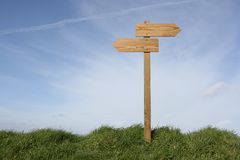 Which direction ?. Wooden direction sign in grass, clipping path included Royalty Free Stock Photography