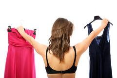 Which dress to choose?. A portrait of a young woman trying to decide between two dresses over white background Royalty Free Stock Photos