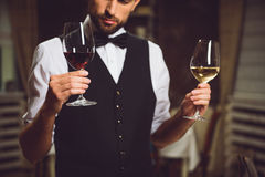 Which glass of wine is better. Sommelier is holding two wineglasses with red and white drink. He looking at it with attention Royalty Free Stock Photos