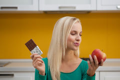 Which one?. Young woman in the kitchen choosing between chocolate and apple. Concept: healthy food Royalty Free Stock Photos