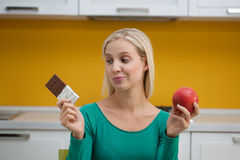 Which one?. Young woman in the kitchen choosing between chocolate and apple. Concept: healthy food Stock Image