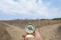 Which road?. Man holding a compass on a fork in the road on a decision, dilemma, direction concept Stock Photos