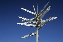 Which Way. A signpost on a hiking path on the South Island of New Zealand gives directions and distances to major ciites around the world. White signs against a Stock Photo