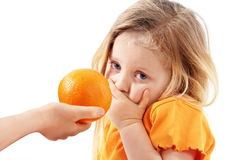 The whimsical child doesn't want to eat orange. The whimsical little girl doesn't want to eat orange Stock Photos