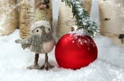 Whimsical Christmas Bird. A whimsical Christmas bird standing with large red ornament (space for copy) that has bent evergreen  branch to snow covered ground Royalty Free Stock Photo