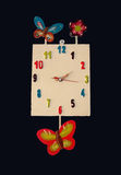 A whimsical clock with a black background. Royalty Free Stock Photo