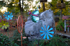 Whimsical Garden Decoration. A metal sculpture of a frog on a bicycle makes a whimsical garden decoration stock images
