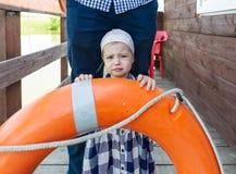 Whimsical little girl and lifebuoy. Horizontal portrait Royalty Free Stock Photography