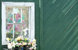 Whimsical Window. Whimsical fake window with colorful curtains, flip flops, and window sill of flowers attached to green fence royalty free stock photos