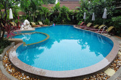 Whimsically curved pool with  clear water. Whimsically curved pool with crystal clear water surrounded by palm trees, statues and sun loungers Stock Photo