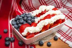 Whip Cream, morangos e mirtilos combinados para olhar como a bandeira americana imagens de stock royalty free