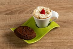 Whipcreamed coffee presented with delectable chocolate scone and a raspberry royalty free stock images