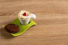 Whipcreamed espresso with delicious chocolate scones on green plate royalty free stock photography