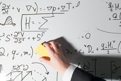 Whiping the whiteboard. Complex math formulas. Mathematics and science. With economics concept. Real equations, symbols handwritten by a professional stock photography