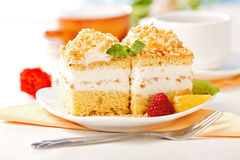 Whipped cream cake garnished with fruit pieces. On small plate royalty free stock image