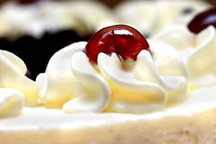 Whipped Cream With Cherry. Close-up of whipped cream with cherry on the cake. Shallow deph of field, focus is on the cherry Stock Photo