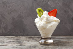Whipped cream in a cup with strawberries and kiwi Royalty Free Stock Photo