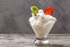 Whipped cream in a cup with strawberries and kiwi Royalty Free Stock Photography