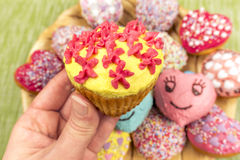 Whipped cream decorated muffin held in hand Stock Photo