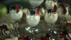 Whipped cream in a glass. Sweet dessert in glass with biscuit,berry fruit and whipped cream. whipped ice cream in glass stock footage