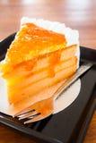 Whipped cream orange marmalade cake. On wooden table royalty free stock image