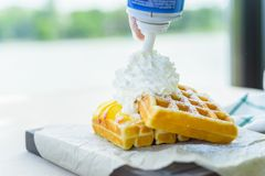Whipped cream put on belgian waffles. Close up hand adds whipped cream on top of belgian waffles with mango Stock Photography