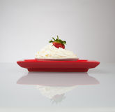 Whipped cream with strawberry on red plate Stock Photo