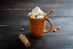 Whipped cream in a wooden mug with a stick of cinnamon and color candies Royalty Free Stock Photo