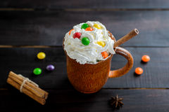 Whipped cream in a wooden mug with a stick of cinnamon and color candies Royalty Free Stock Image