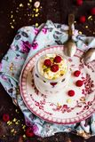 Whipped mascarpone cream cheese with white chocolate, fresh raspberry and pistachios in a jar, selective focus. Whipped mascarpone cream cheese with white royalty free stock images