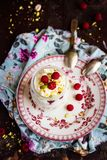 Whipped mascarpone cream cheese with white chocolate, fresh raspberry and pistachios in a jar, selective focus. Whipped mascarpone cream cheese with white stock photo