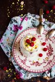 Whipped mascarpone cream cheese with white chocolate, fresh raspberry and pistachios in a jar. Selective focus Stock Image