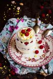 Whipped mascarpone cream cheese with white chocolate, fresh raspberry and pistachios in a jar. Selective focus Royalty Free Stock Photo