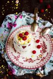 Whipped mascarpone cream cheese with white chocolate, fresh raspberry and pistachios in a jar. Selective focus stock images