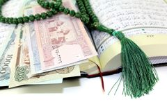 Whipped Quran with afghanistanischer currency Royalty Free Stock Photos